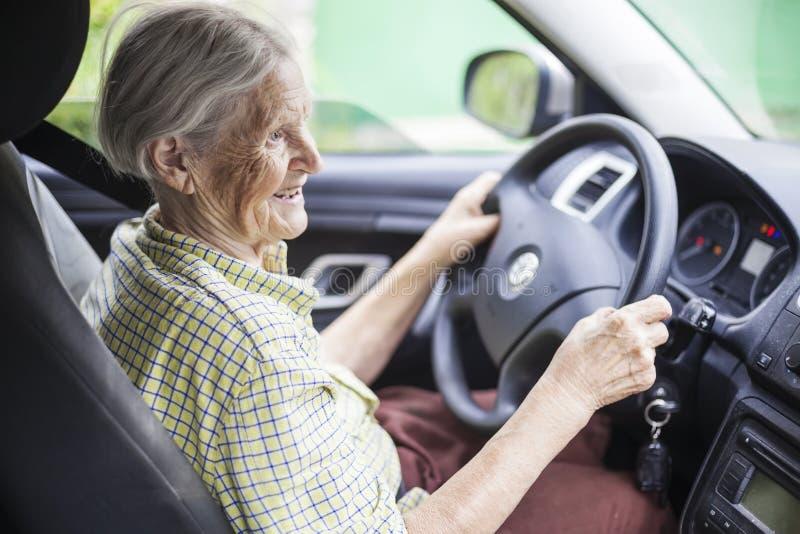 Mujer mayor alegre que conduce un coche fotografía de archivo libre de regalías