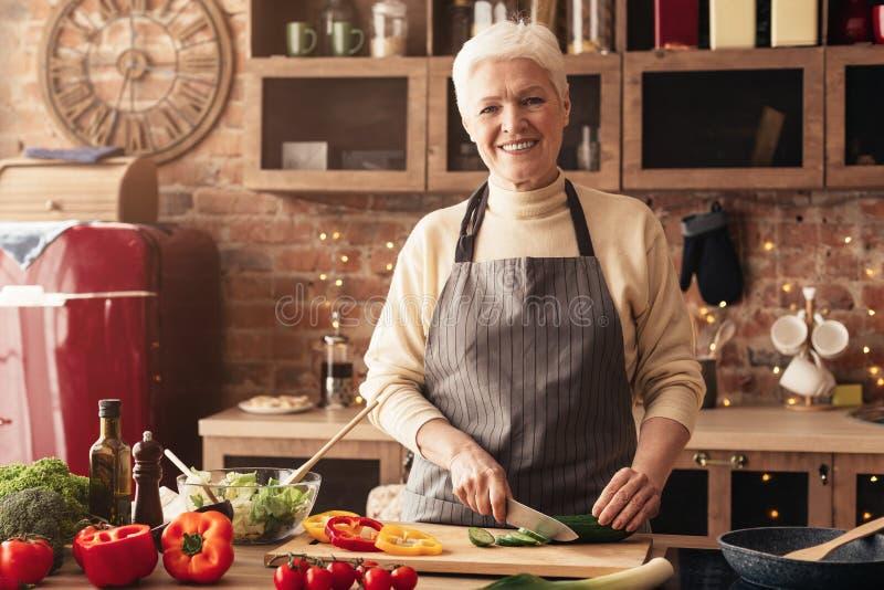 Mujer mayor alegre que corta las verduras para la ensalada imagenes de archivo