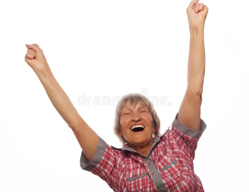 Mujer mayor alegre que gesticula la victoria sobre un fondo blanco fotos de archivo