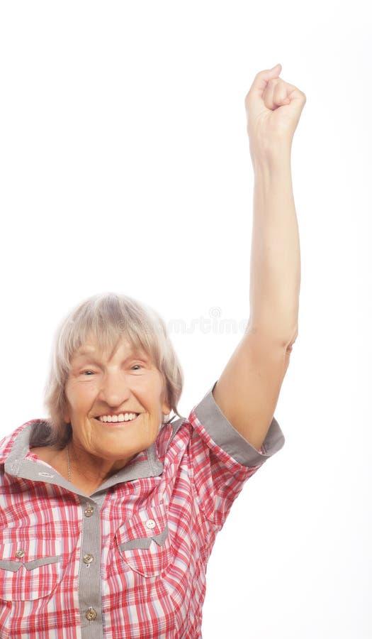 Mujer mayor alegre que gesticula la victoria sobre un fondo blanco fotos de archivo libres de regalías