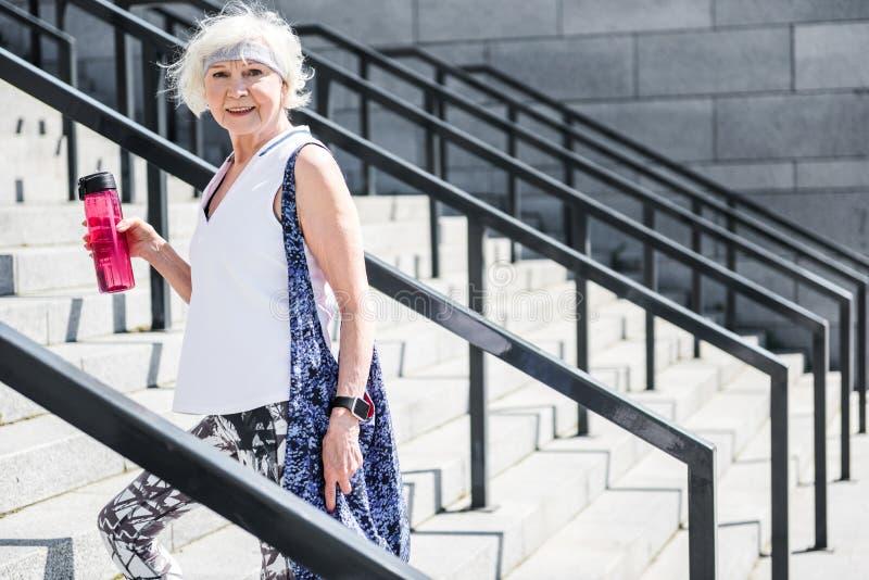 Mujer mayor alegre que se coloca en las escaleras al aire libre fotos de archivo libres de regalías