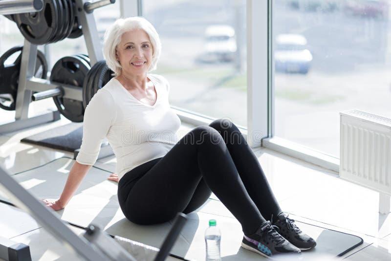 Mujer mayor alegre que se relaja en el gimnasio fotos de archivo libres de regalías