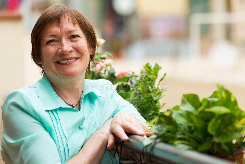 Mujer mayor alegre que se sienta en balcón imagen de archivo