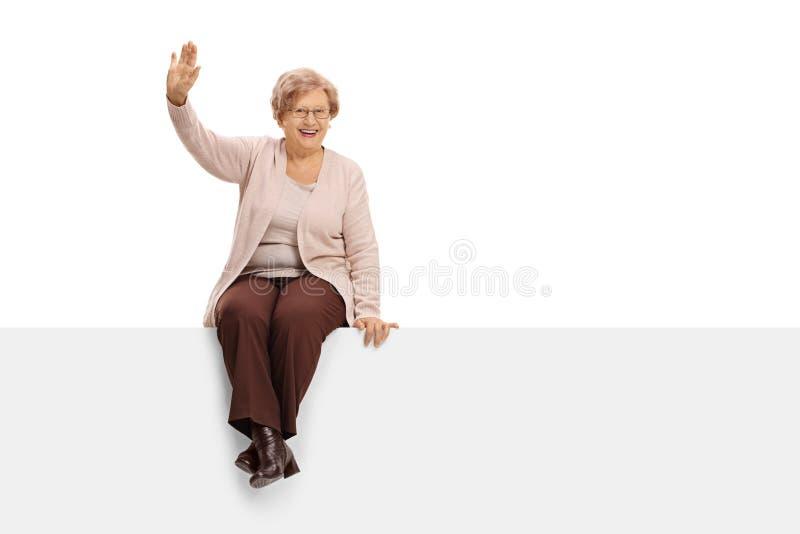 Mujer mayor alegre que se sienta en un panel y agitar imagen de archivo