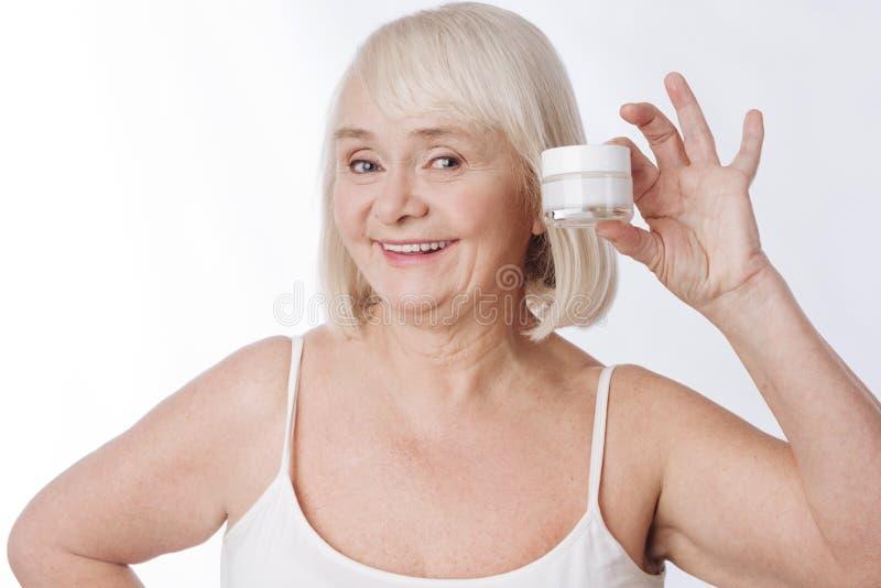 Mujer mayor alegre que sostiene una botella poner crema foto de archivo