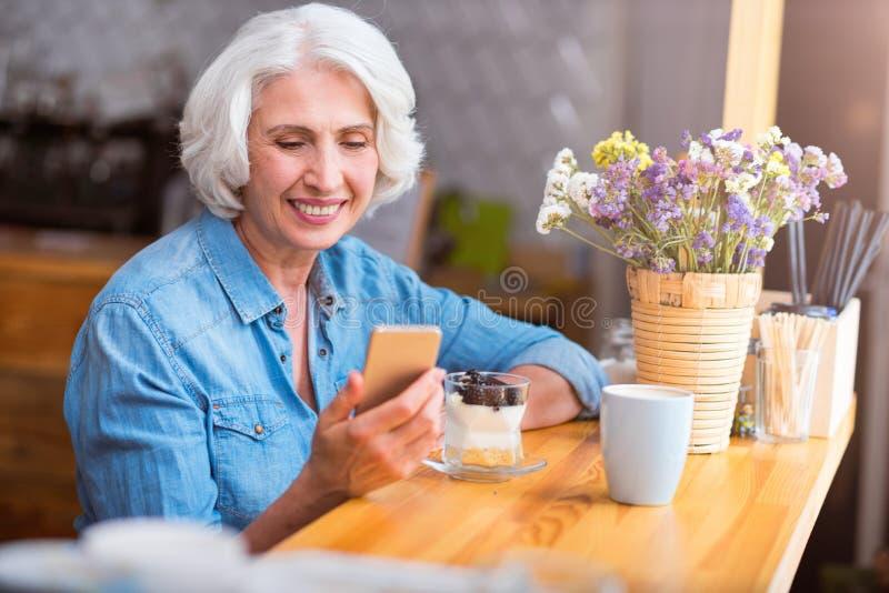 Mujer mayor alegre que usa el teléfono celular fotografía de archivo libre de regalías