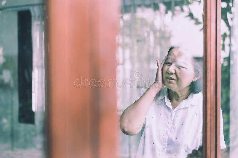 Mujer mayor asiática madura que tiene un dolor del dolor de cabeza, concepto sano mayor imagenes de archivo
