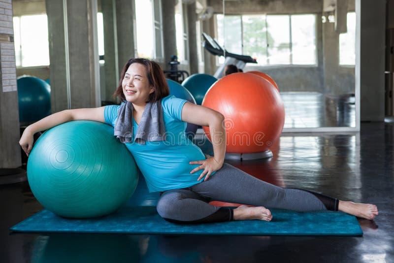 mujer mayor asiática que hace yoga en gimnasio de la aptitud ejercicio envejecido de la se?ora Viejo entrenamiento femenino Entre imagen de archivo
