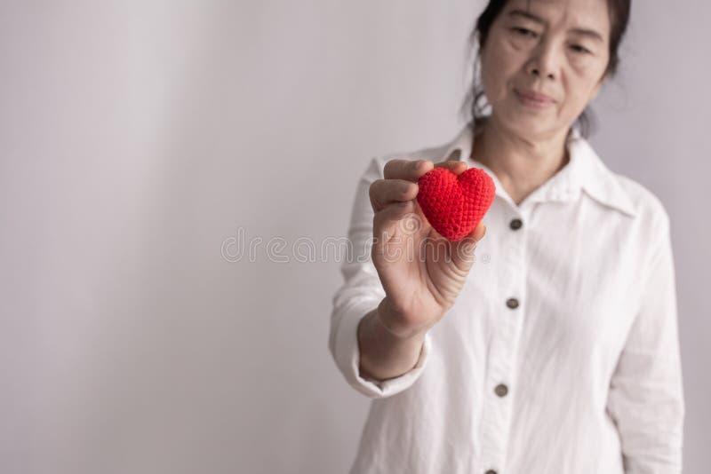 Mujer mayor asiática que lleva a cabo la forma roja del corazón, concepto de concepto de la enfermedad cardíaca de la prevención fotografía de archivo libre de regalías