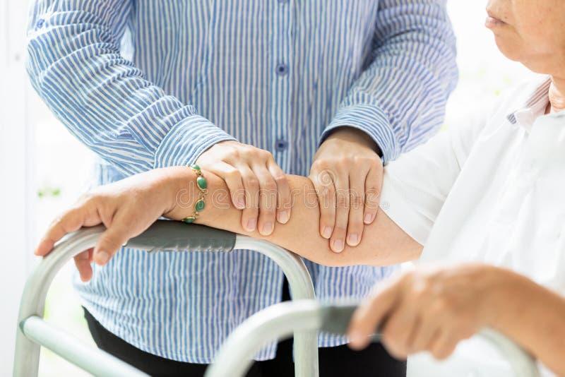 Mujer mayor asi?tica que recibe masaje del terapeuta de sexo femenino del physic de su brazo y mano debido a lesi?n, personas may imagenes de archivo