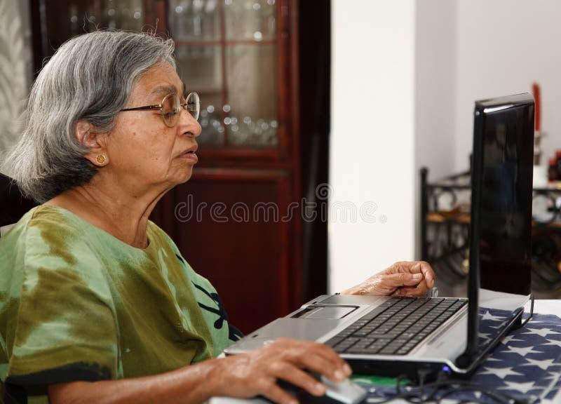 Mujer mayor asiática que usa el ordenador fotos de archivo libres de regalías