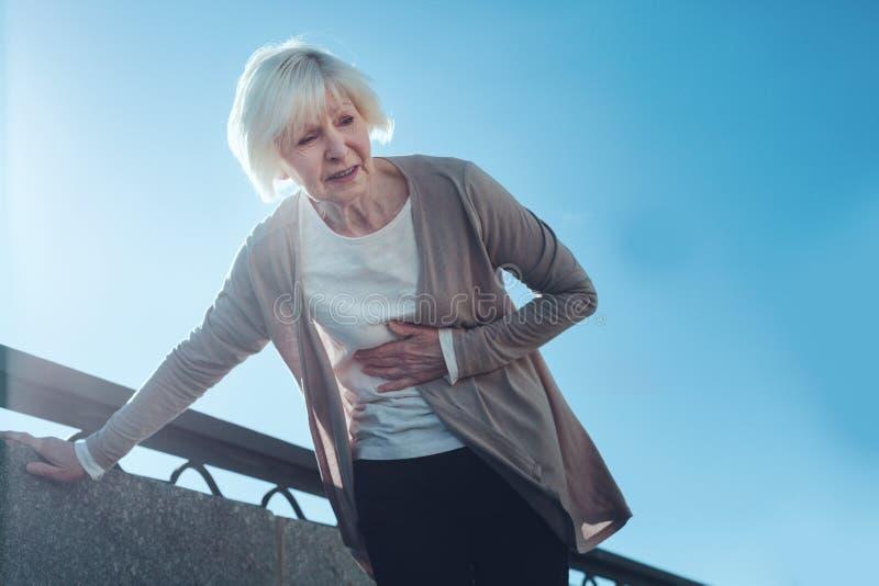Mujer mayor asustada que tiene ataque del corazón al aire libre fotografía de archivo libre de regalías