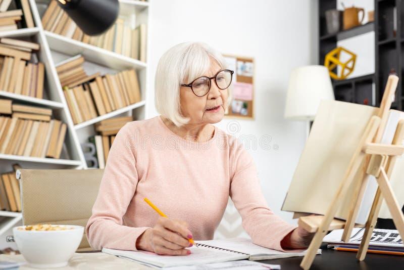 Mujer mayor atenta que comprueba lexis fotos de archivo libres de regalías
