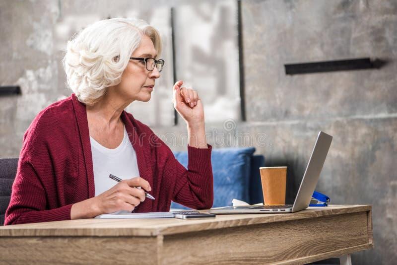Mujer mayor atenta que hace notas y la mirada imagen de archivo
