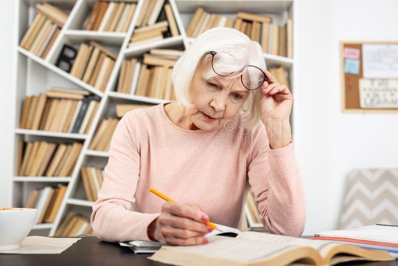 Mujer mayor atenta que tiene problema en estudio imagen de archivo libre de regalías