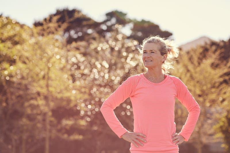 Mujer mayor atlética que mira aire libre confiado en un MOR iluminado por el sol fotografía de archivo libre de regalías