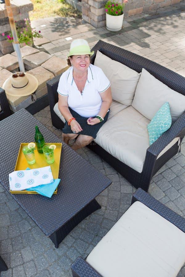 Mujer mayor atractiva amistosa en un patio imágenes de archivo libres de regalías