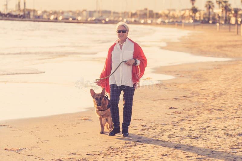 Mujer mayor atractiva feliz con su perro alemán del shepard que camina en la playa en la puesta del sol del otoño imagenes de archivo