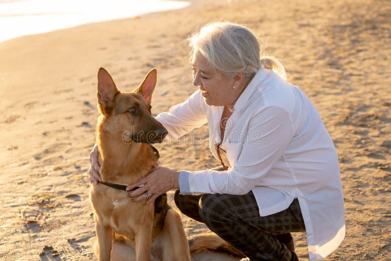 Mujer mayor atractiva feliz del retrato o con su perro alemán del shepard en la playa en la puesta del sol del otoño fotos de archivo