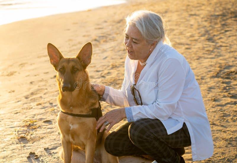 Mujer mayor atractiva feliz del retrato o con su perro alemán del shepard en la playa en la puesta del sol del otoño imagen de archivo libre de regalías