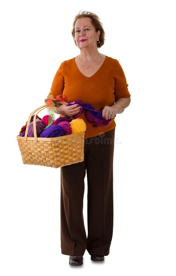 Mujer mayor atractiva que sostiene una cesta de lanas fotografía de archivo libre de regalías