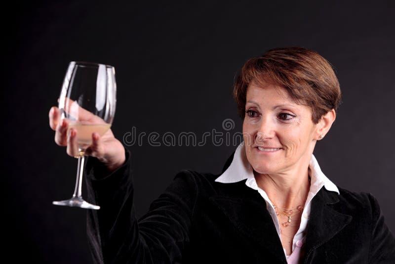 Mujer mayor bonita que sube encima de un vidrio de vino (cara del foco) imagen de archivo