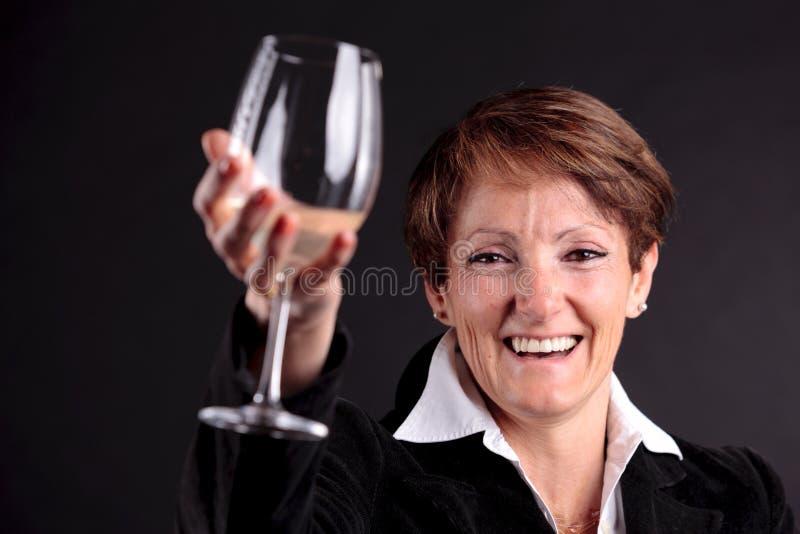 Mujer mayor bonita que sube encima de un vidrio del vino (foco en cara) foto de archivo
