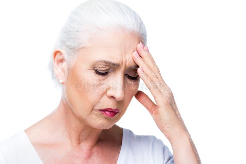 Mujer mayor cansada con dolor de cabeza fotografía de archivo