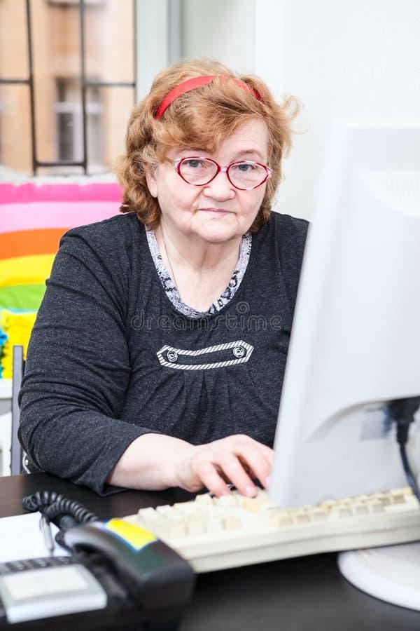 Mujer mayor caucásica que trabaja con el ordenador imagen de archivo libre de regalías