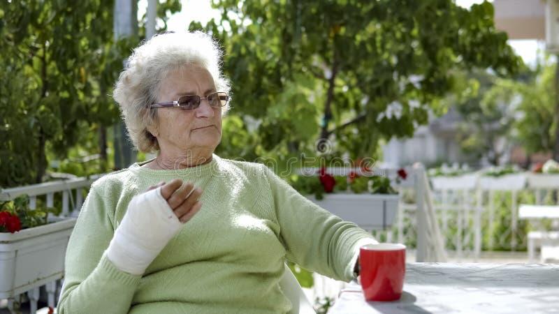 Mujer mayor mayor con café de consumición herido de la mano fotografía de archivo