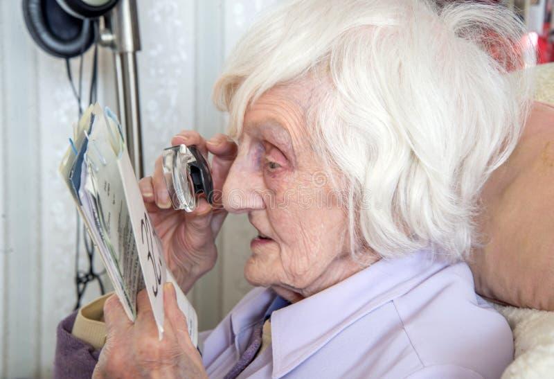 Mujer mayor con deficiencias visuales con el magnifyer fotos de archivo libres de regalías