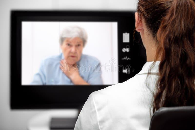 Mujer mayor con disnea, doctor que mira el escritorio, telemedi imágenes de archivo libres de regalías