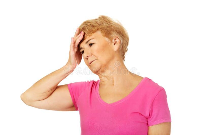 Mujer mayor con dolor de cabeza enorme fotos de archivo libres de regalías