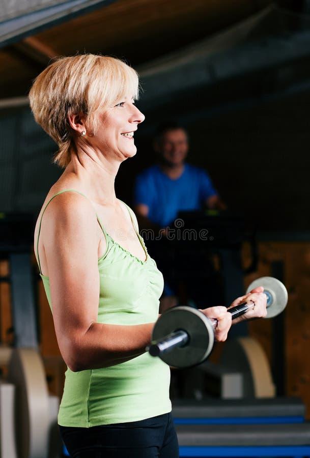 Mujer mayor con el barbell en gimnasia fotografía de archivo libre de regalías