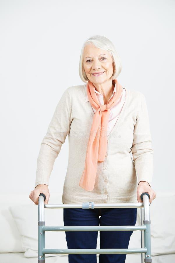 Mujer mayor con el caminante en casa fotografía de archivo