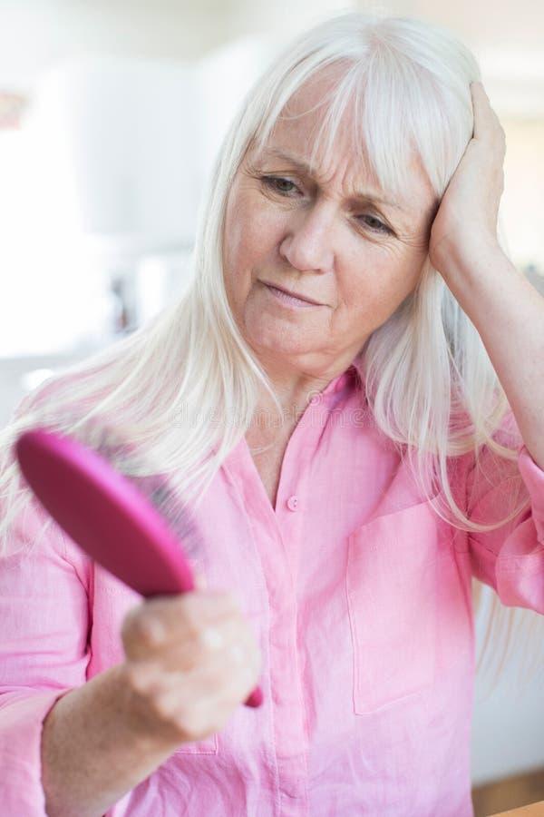 Mujer mayor con el cepillo referido sobre pérdida de pelo imagen de archivo