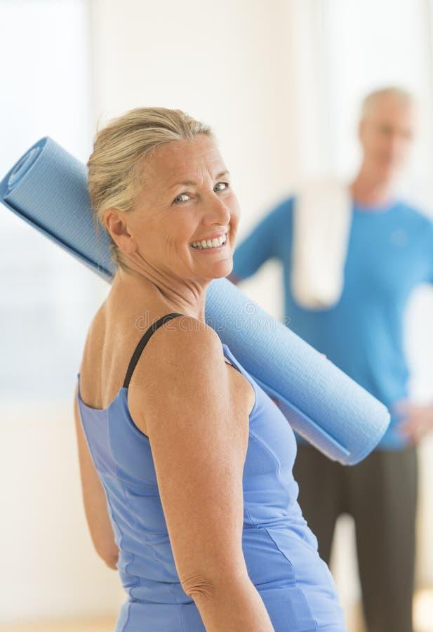 Mujer mayor con el ejercicio Mat At Home fotos de archivo libres de regalías