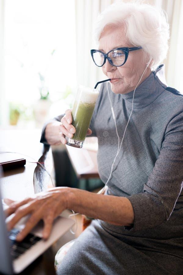 Mujer mayor con el jugo fresco fotos de archivo libres de regalías