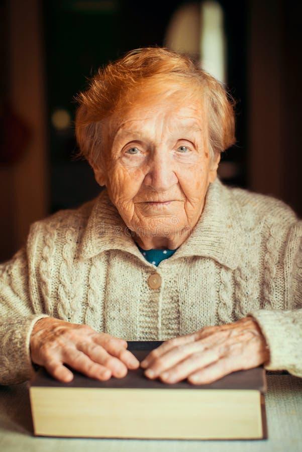 Mujer mayor con el libro que se sienta en la tabla foto de archivo libre de regalías