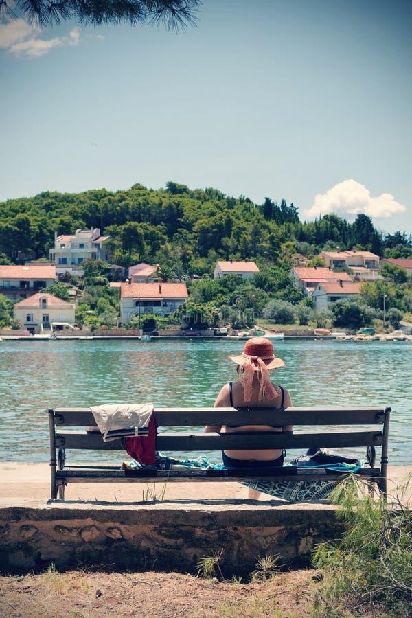 Mujer mayor con el sombrero de paja que se sienta en banco por el mar y que disfruta de la visión imagen de archivo libre de regalías