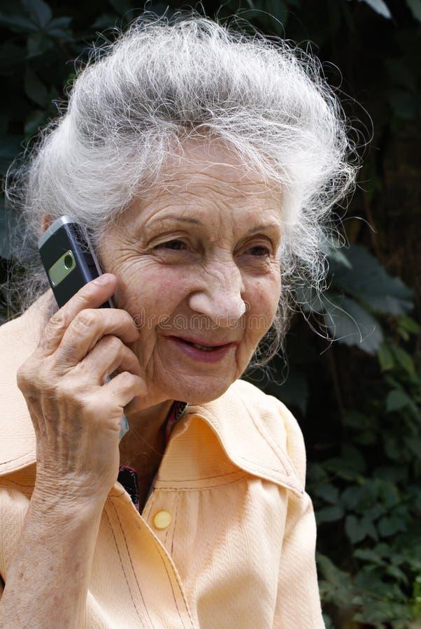 Mujer mayor con el teléfono celular imagenes de archivo