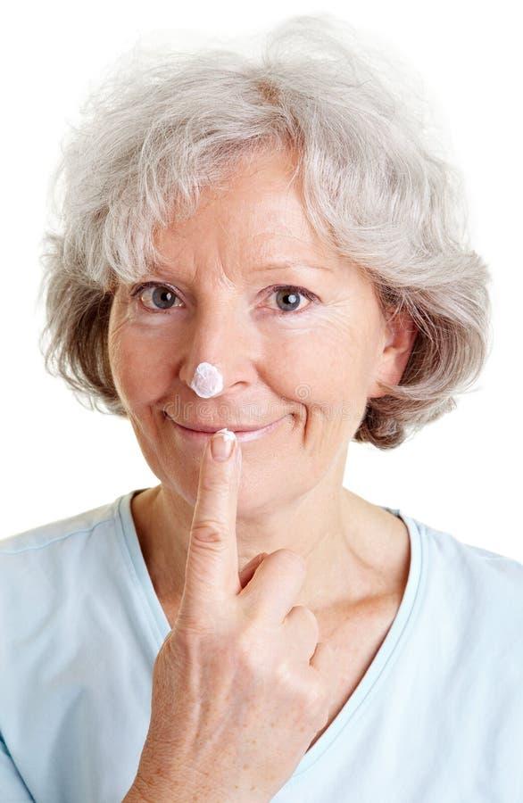 Mujer mayor con gota de la loción encendido foto de archivo