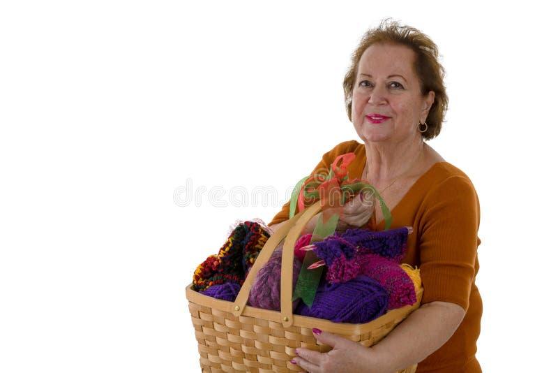 Mujer mayor con hilado en cesta fotografía de archivo