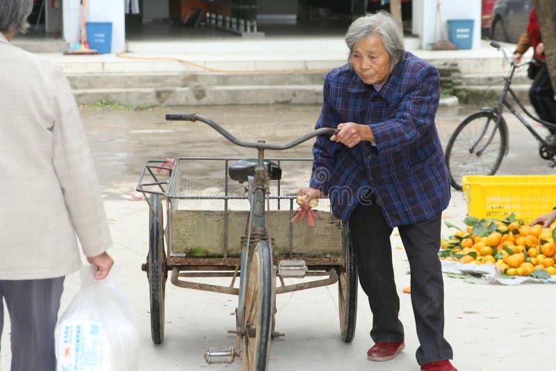 Mujer mayor con la bici y el remolque en el mercado de Xingping en China foto de archivo libre de regalías