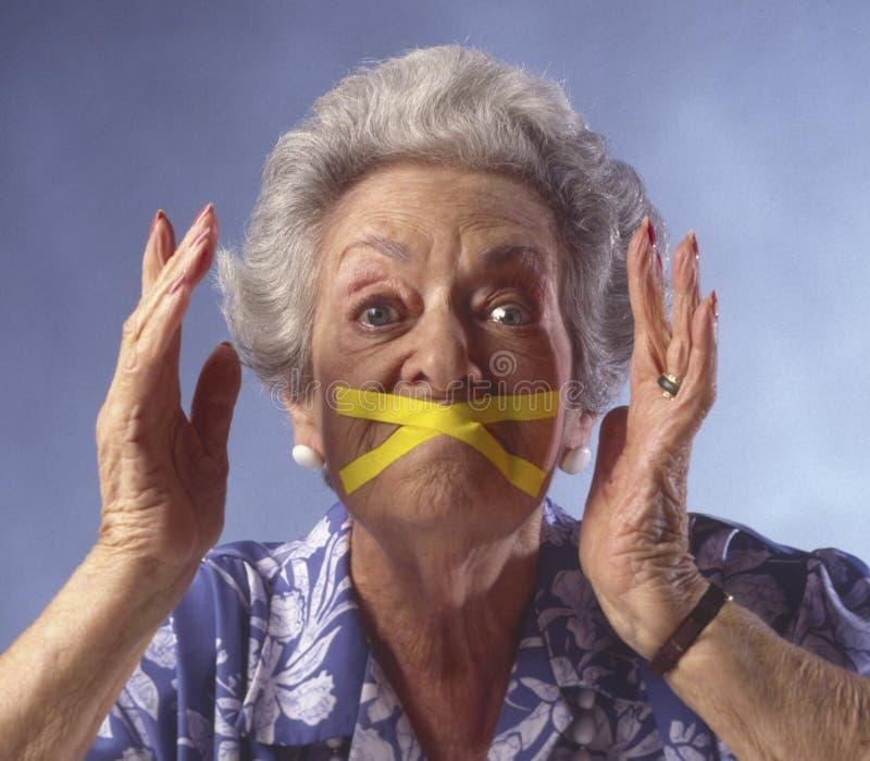 Mujer mayor con la boca sujetada con cinta adhesiva cerrada fotos de archivo libres de regalías