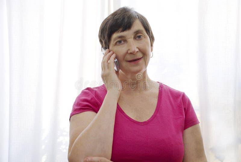 Mujer mayor con la célula foto de archivo libre de regalías