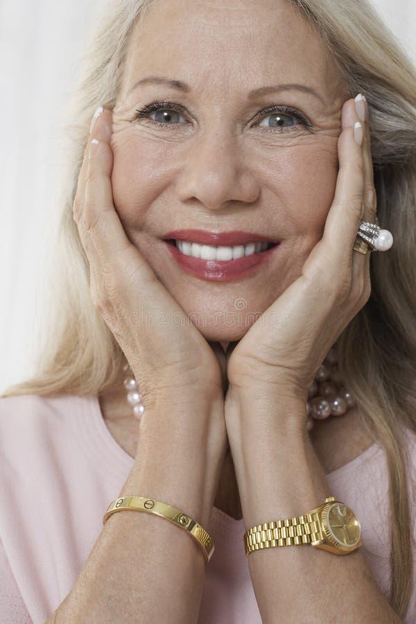 Mujer mayor con la cara en manos fotografía de archivo