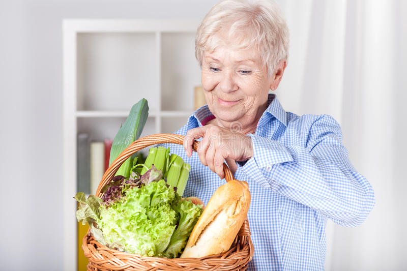 Mujer mayor con la cesta de compras imagenes de archivo