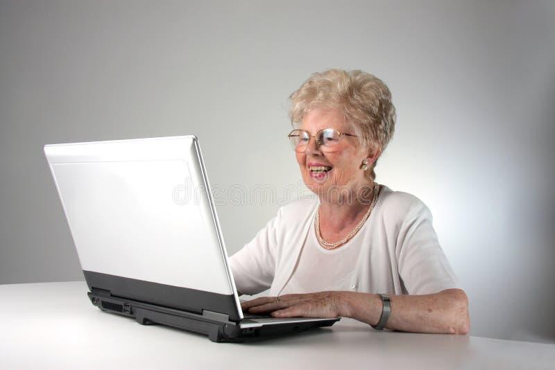 Mujer mayor con la computadora portátil fotografía de archivo