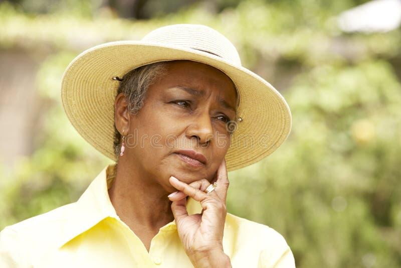Mujer mayor con la expresión pensativa imagenes de archivo